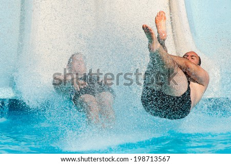 People having fun, sliding at water park. - stock photo