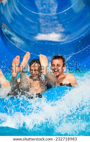 People having fun, water sliding at aqua park. - stock photo