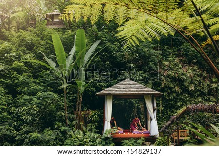 People having massage at spa resort surrounded by trees. Outdoor spa center at luxury resort. - stock photo