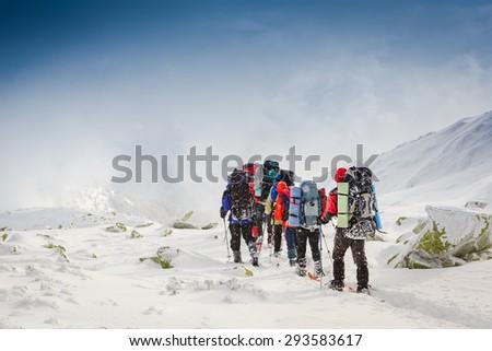 people hiking in beautiful mountain winter landscape - stock photo