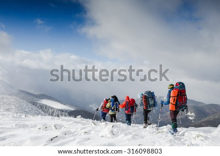 people hiking in beautiful winter mountains - stock photo