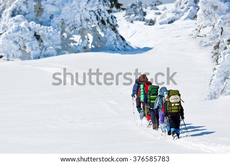 people hiking in winte mountains - stock photo