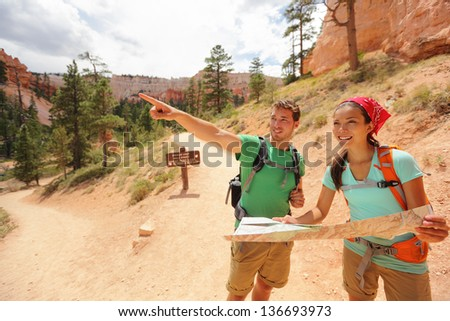 People hiking looking at hike map in Bryce Canyon. Young multiracial couple of hikers navigating and smiling happy during hike in Bryce Canyon National Park landscape, Utah, USA. Young woman and man. - stock photo