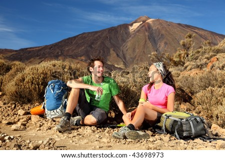 People hiking. Young beautiful couple taking a break, relaxing and eating during a hike / backpacking trip in the beautiful volcanic landscape in the national park on the volcano, Teide, Tenerife. - stock photo