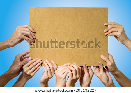 People holding blank bord on blue background - stock photo