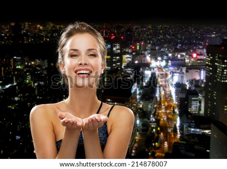 people, holidays, advertisement and luxury concept - laughing woman in evening dress holding something imaginary over night city background - stock photo