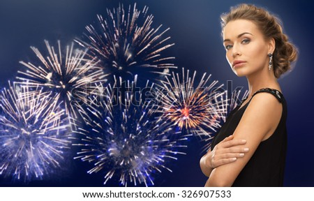 people, holidays and glamour concept - beautiful woman wearing earrings over firework on dark blue background - stock photo