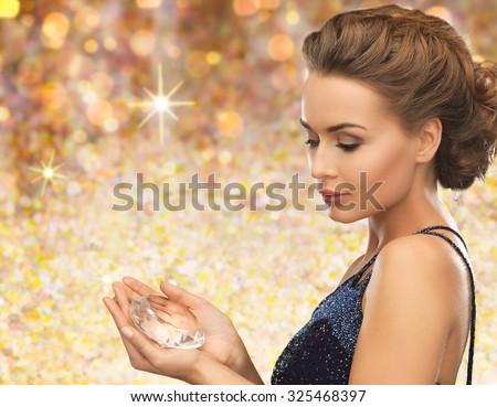 people, holidays and glamour concept - smiling woman in evening dress with diamond crystal over golden lights background - stock photo