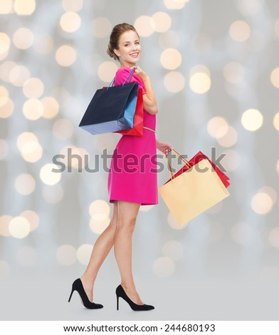 people, holidays and sale concept - young happy woman with shopping bags over holidays lights background - stock photo