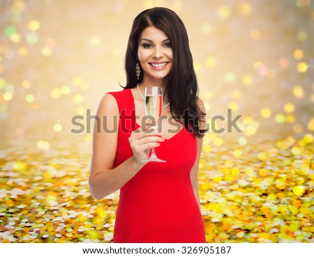 people, holidays, christmas and celebration concept - beautiful sexy woman in red dress with champagne glass over golden glitter or lights background - stock photo