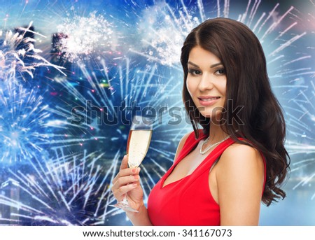 people, holidays, christmas, new year party and celebration concept - beautiful sexy woman in red dress with champagne glass over night city and firework background - stock photo
