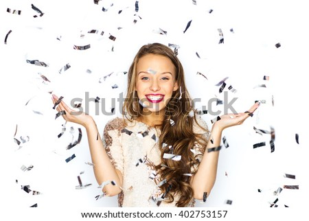 people, holidays, emotion and glamour concept - happy young woman or teen girl in fancy dress with sequins and confetti at party - stock photo