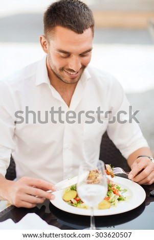 people, holidays, food and leisure concept - happy man with fork and knife eating salad for dinner at restaurant terrace - stock photo