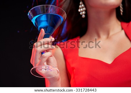 people, holidays, party, alcohol and leisure concept - close up of woman with cocktail at nightclub - stock photo