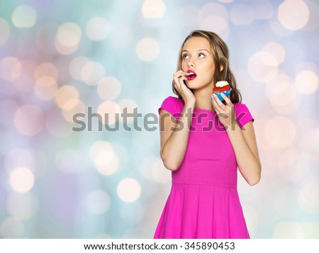 people, holidays, party, junk food and celebration concept - happy young woman or teen girl in pink dress with birthday cupcake over holidays lights background - stock photo