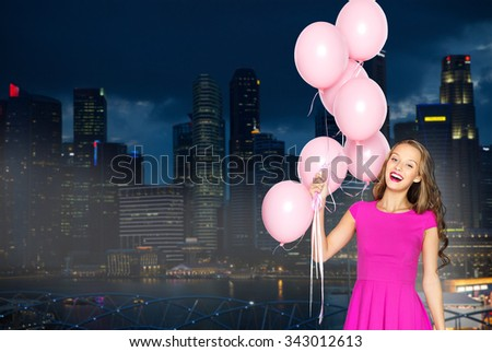 people, holidays, party, nightlife and fashion concept - happy young woman or teen girl in pink dress with helium air balloons over night singapore city background - stock photo