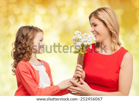 people, holidays, relations and family concept - happy little daughter giving flowers to her mother over yellow lights background - stock photo