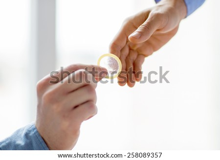 people, homosexuality, safe sex, sexual education and charity concept - close up of happy male gay couple hands giving condom - stock photo