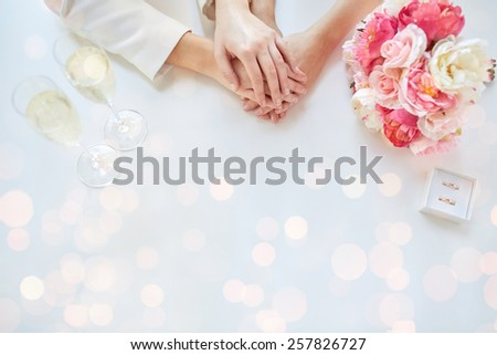 people, homosexuality, same-sex marriage and love concept - close up of happy lesbian couple hands with flower bunch, champagne glasses and wedding rings over holiday lights background - stock photo