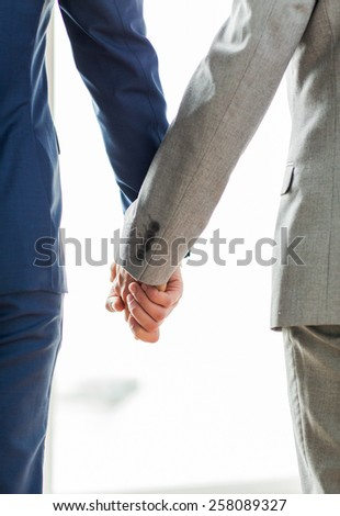 people, homosexuality, same-sex marriage and love concept - close up of happy male gay couple holding hands from back - stock photo