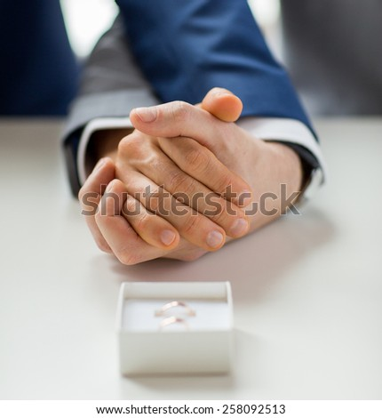 people, homosexuality, same-sex marriage and love concept - close up of happy male gay couple holding hands and wedding rings in box on table - stock photo