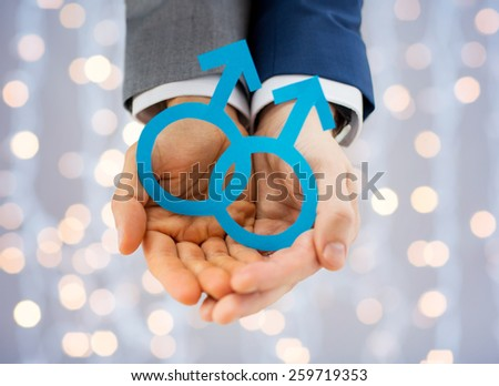 people, homosexuality, same-sex marriage and love concept - close up of happy male gay couple holding paper cutout love symbol over holidays lights background - stock photo
