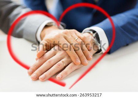 people, homosexuality, same-sex marriage and love concept - close up of happy male gay couple hands with wedding rings on and red heart shape - stock photo