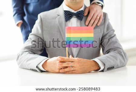 people, homosexuality, same-sex marriage and love concept - close up of happy male gay couple in suits and bow-ties with wedding ring holding rainbow flag - stock photo