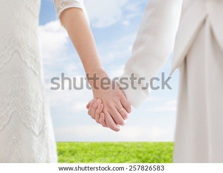 people, homosexuality, same-sex marriage and love concept - close up of happy married lesbian couple holding hands with wedding ring on over blue sky and grass background - stock photo
