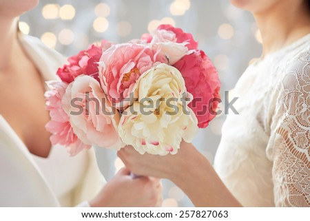 people, homosexuality, same-sex marriage and love concept - close up of happy married lesbian couple with flower bunch over holiday lights background - stock photo