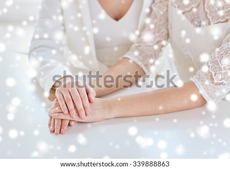 people, homosexuality, same-sex marriage and love concept - close up of happy married lesbian couple hands over snow effect - stock photo