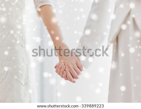 people, homosexuality, same-sex marriage and love concept - close up of happy married lesbian couple hugging over snow effect - stock photo