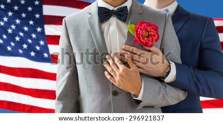people, homosexuality, same-sex marriage and love concept - close up of happy married male gay couple in suits with buttonholes and bow-ties on wedding over american flag background - stock photo