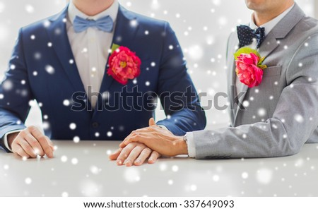 people, homosexuality, same-sex marriage and love concept - close up of happy married male gay couple in suits with buttonholes and bow-ties holding hands on wedding over snow effect - stock photo