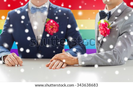 people, homosexuality, same-sex marriage and love concept - close up of happy married male gay couple in suits with buttonholes holding hands on wedding over rainbow flag background and snow effect - stock photo