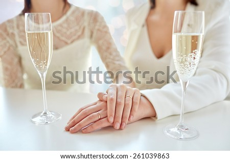 people, homosexuality, same-sex marriage, celebration and love concept - close up of happy married lesbian couple hands on top and champagne glasses over holiday lights background - stock photo