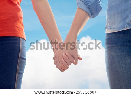people, homosexuality, same-sex marriage, gay and love concept - close up of happy lesbian couple holding hands over blue sky and cloud background - stock photo