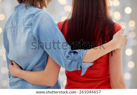 people, homosexuality, same-sex marriage, gay and love concept - close up of happy lesbian couple hugging at home over holidays lights background - stock photo