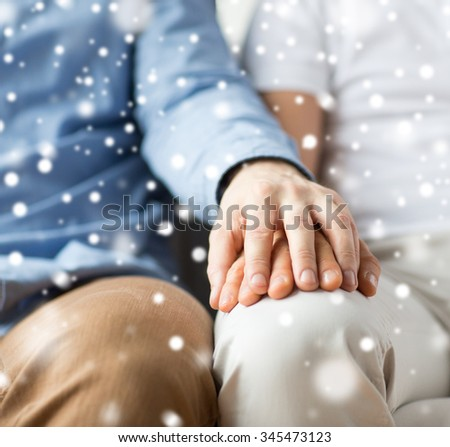 people, homosexuality, same-sex marriage, gay and love concept - close up of happy male gay couple holding hands over snow effect - stock photo