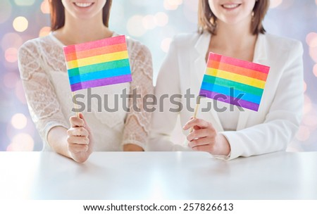 people, homosexuality, same-sex marriage, gay pride and love concept - close up of happy lesbian couple holding rainbow flags over holiday lights background - stock photo