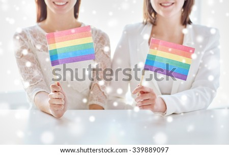 people, homosexuality, same-sex marriage, gay pride and love concept - close up of happy lesbian couple holding rainbow flags over snow effect - stock photo