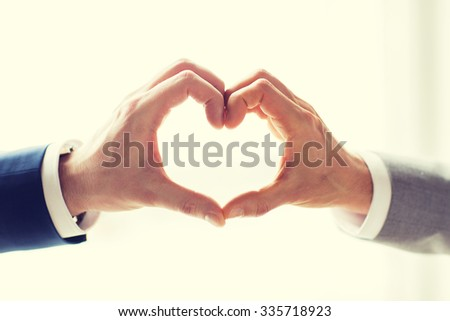 people, homosexuality, same-sex marriage, gesture and love concept - close up of happy male gay couple hands showing heart hand sign - stock photo