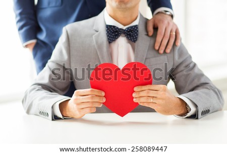 people, homosexuality, same-sex marriage, valentines day and love concept - close up of happy married male gay couple with red paper heart shape on wedding - stock photo