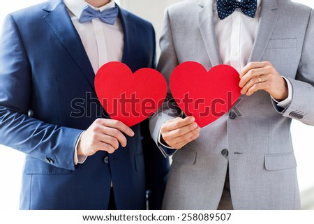 people, homosexuality, same-sex marriage, valentines day and love concept - close up of happy married male gay couple holding red paper heart shapes on wedding - stock photo