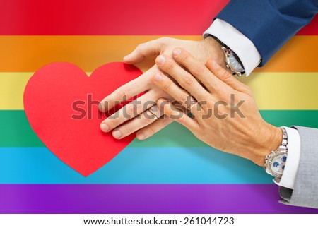 people, homosexuality, same-sex marriage, valentines day and love concept - close up of happy married male gay couple hands with red paper heart shape over rainbow flag background - stock photo