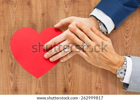 people, homosexuality, same-sex marriage, valentines day and love concept - close up of happy married male gay couple hands with red paper heart shape over wooden background - stock photo