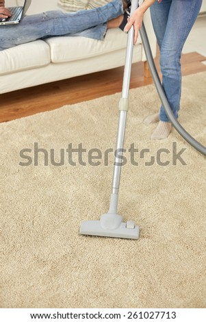 people, housework and housekeeping concept - close up of couple legs and vacuum cleaner on carpet at home - stock photo