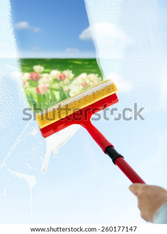 people, housework and housekeeping concept -close up of hand cleaning window glass with sponge mop and foam over blue sky and flower field background - stock photo