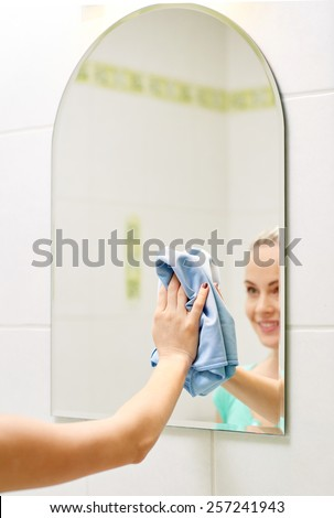 people, housework and housekeeping concept - close up of happy woman cleaning mirror with rag at home - stock photo