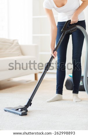 people, housework and housekeeping concept - close up of woman with vacuum cleaner cleaning carpet at home - stock photo
